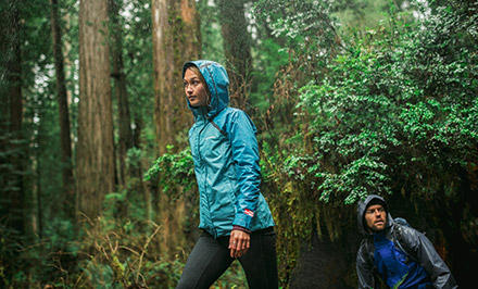 A man and woman in OutDry gear hiking in a forest.