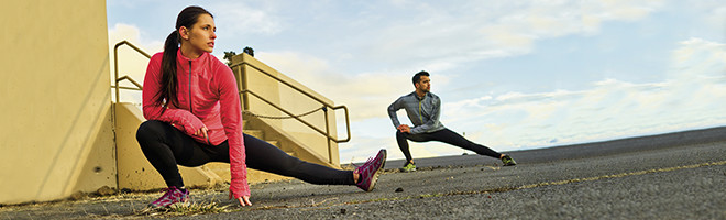 A woman and a man in workout clothes stretching outside.