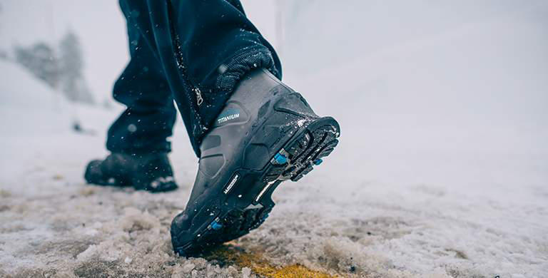 A man wearing shoes with Michelin outsoles in the snow.