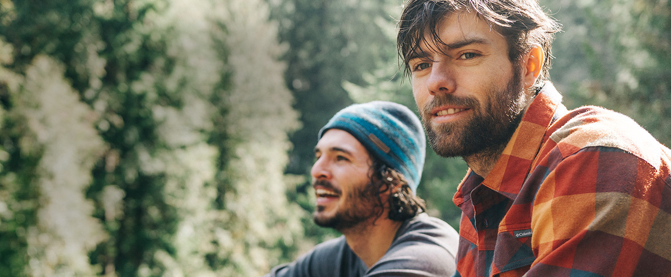 Two smiling, bearded young men in the forest.