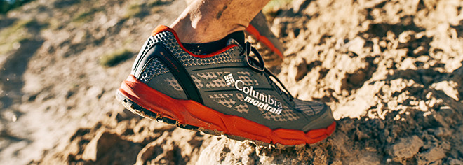 Closeup of  trail running shoe climbing over rocks.