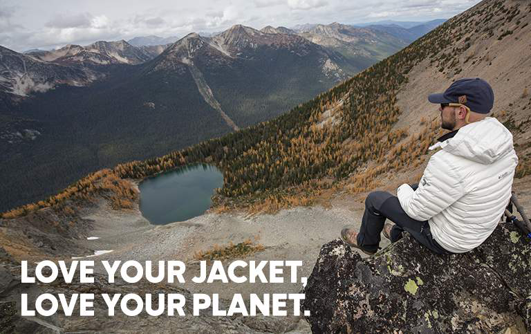 A man wearing a white OutDry Extreme Eco Down jacket sits on a rock outcrop and looks out at a mountain valley and lake below him.
