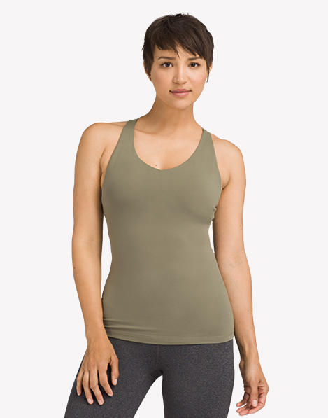 A woman wearing a dark green, fitted yoga tank top.