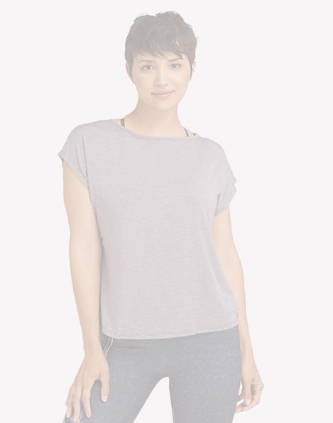A woman wearing a gray short-sleeve, looser fitting yoga top.