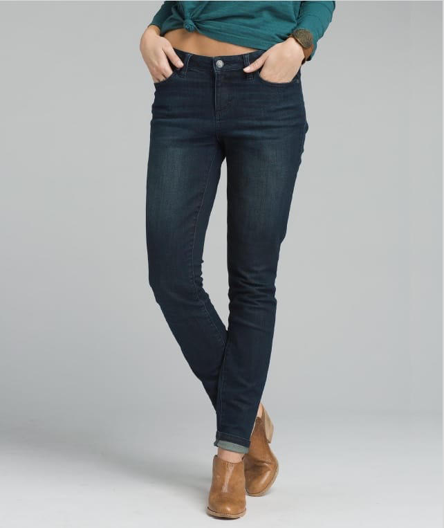 A woman wearing straight-leg skinny jeans with brown wedge shoes.