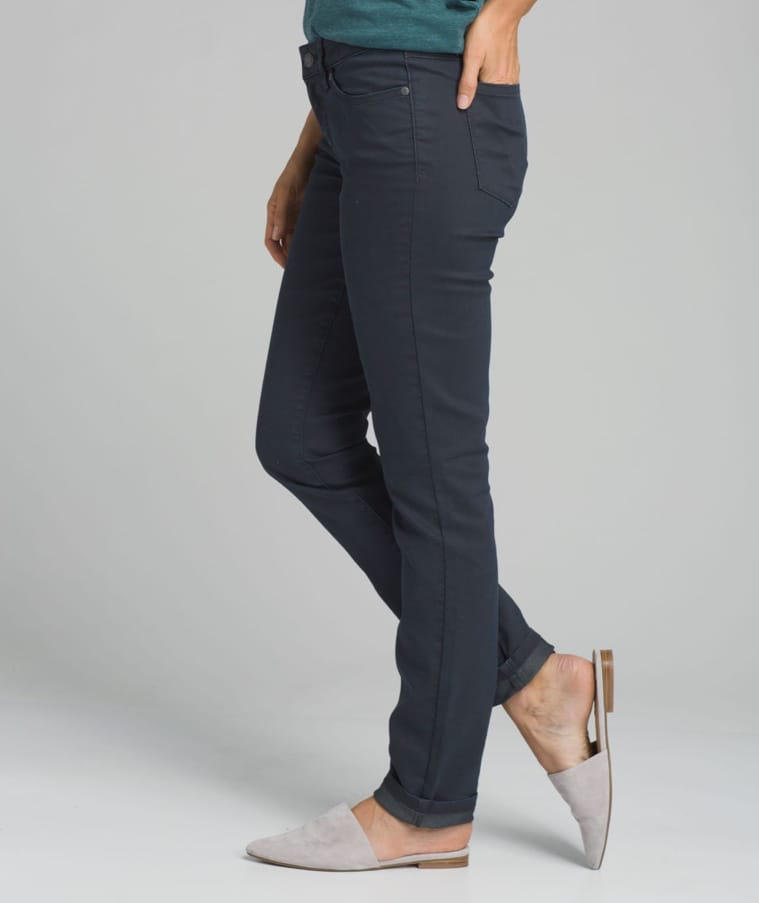 A woman wearing straight-leg, dark colored denim with off-white mules.