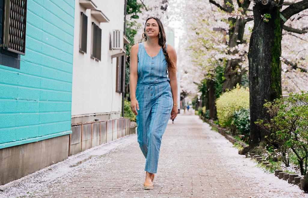 a3e61d29da80d A woman wearing a blue romper walks down a neighborhood street. Shop Women's