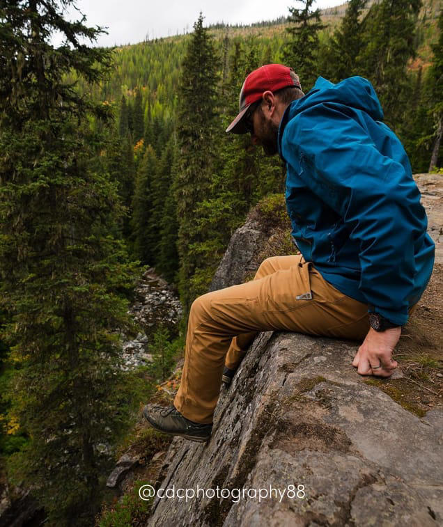 A man hikes and bouldering in a forest in Stretch Zion pants