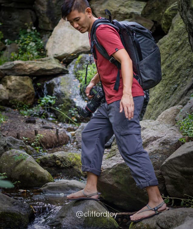 A man hikes through a rocky green valley across a stream in Stretch Zion pants