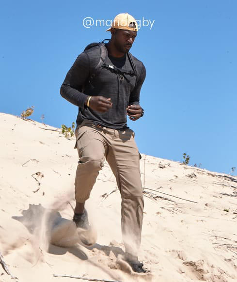 A man hikes down a sand dune in Stretch Zion pants