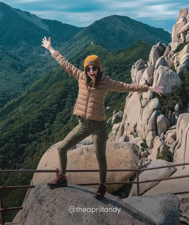 A woman summits a peak in Stretch Zion pants