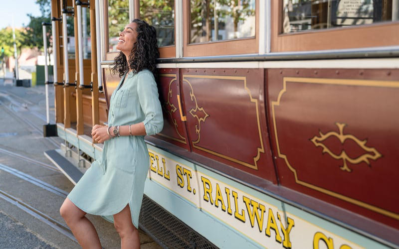 A woman wearing a light blue sun dress leans on a trolley in San Francisco.