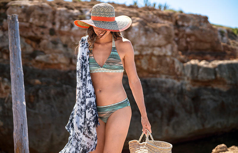 A woman wearing a patterned bikini and sun hat stands on beach.