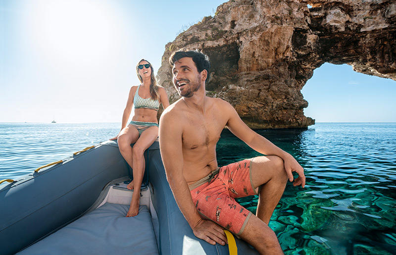 A man and woman sit on an inflatable boat in the sea of Mallorca.