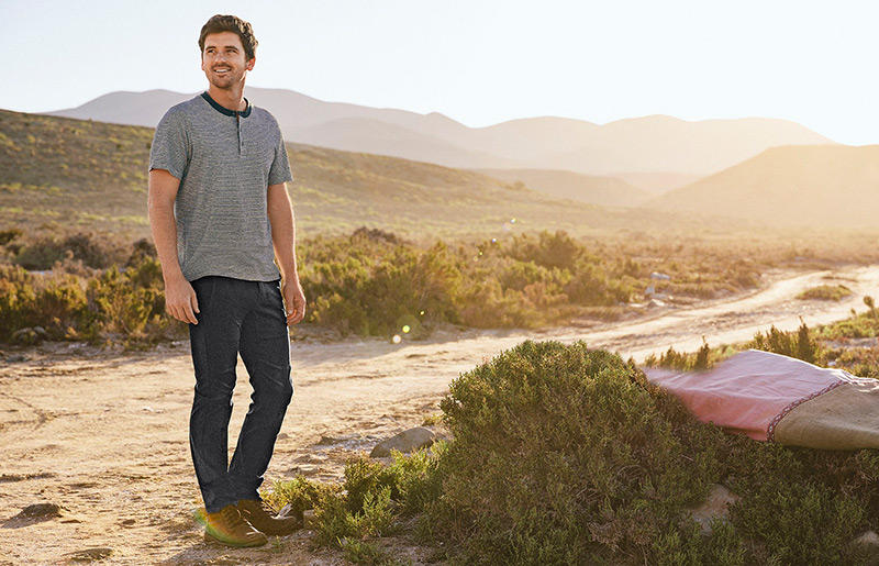 Man in solid shirt and jeans explores the desert with his surfboard.