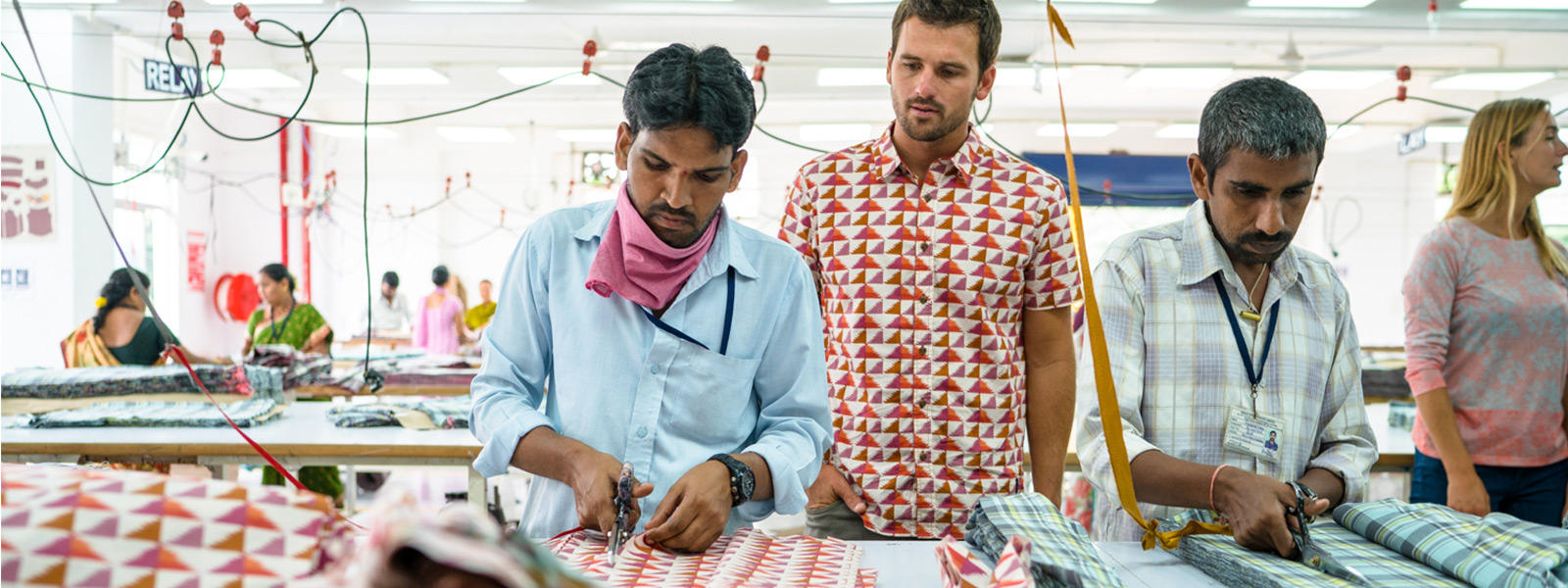 two men cut fabric for geo print button-up in a factory in India