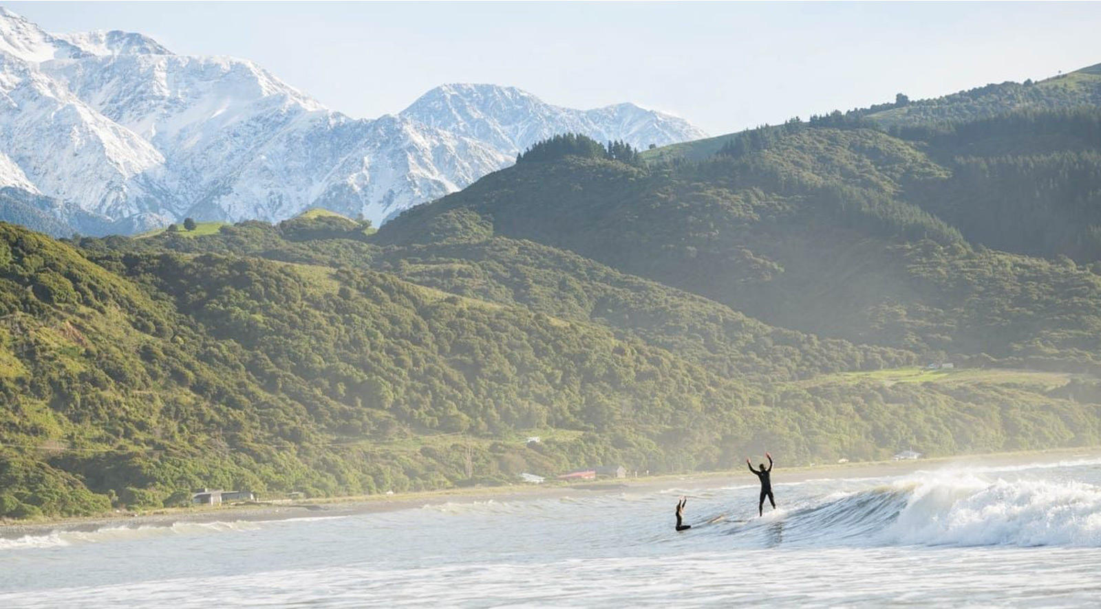 two surfers celebrate great waves with lush hills and snow-capped mountains on the horizon
