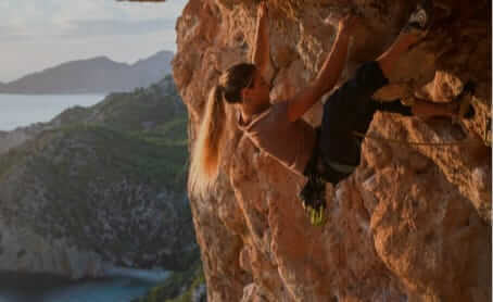 prAna Ambassador Rannveig Aamodt sport climbs high above the Balearic Sea on Mallorca.