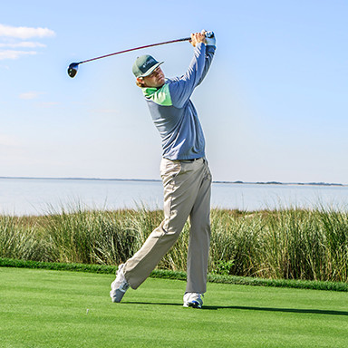 A man swinging a golf club on a golf course.