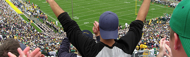 People cheering for their team at a football game.