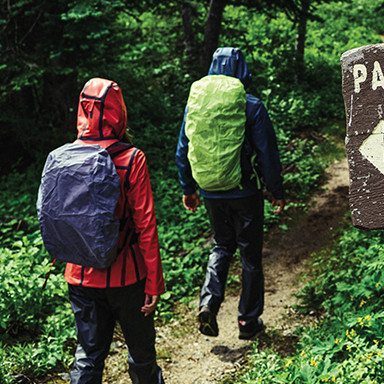 Two hikers in raingear walking on a trail on a rainy day.