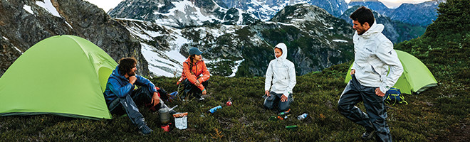 A group of people in rain jackets camping on a mountain top.