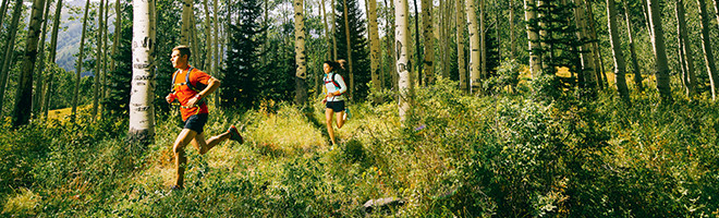 A man and a woman running on a trail through the woods.