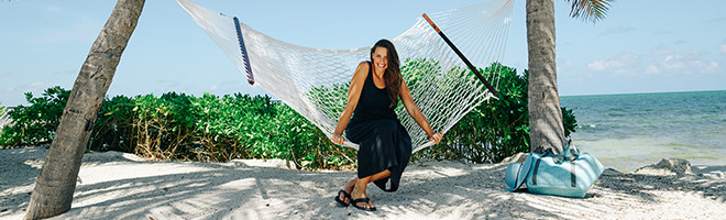 A smiling woman in a hammock on a tropical beach.