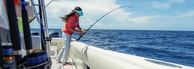 A woman fishing off a boat in a pink shirt, PFG logo, Discover PFG link.