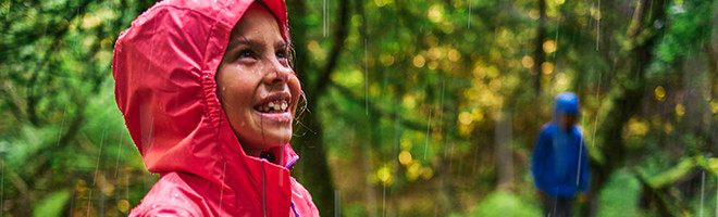 A smiling girl in a rain jacket walking in the rain in a forest.