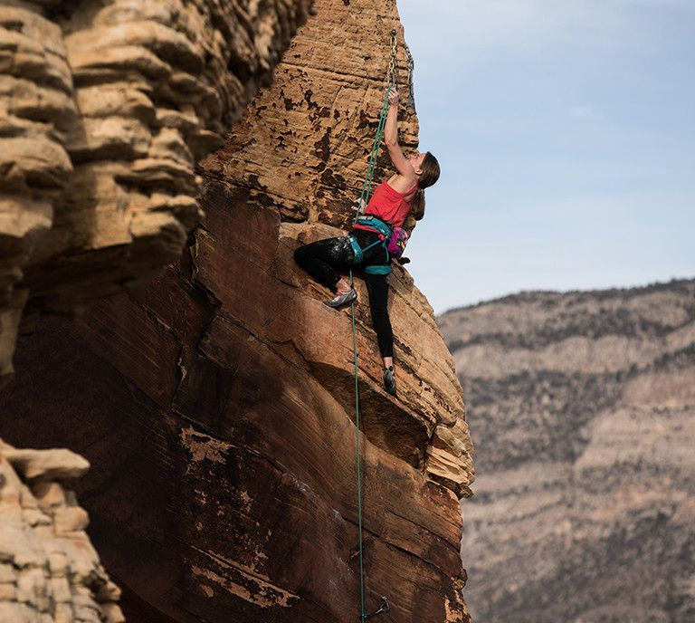 A woman in pants climbing a rock face.