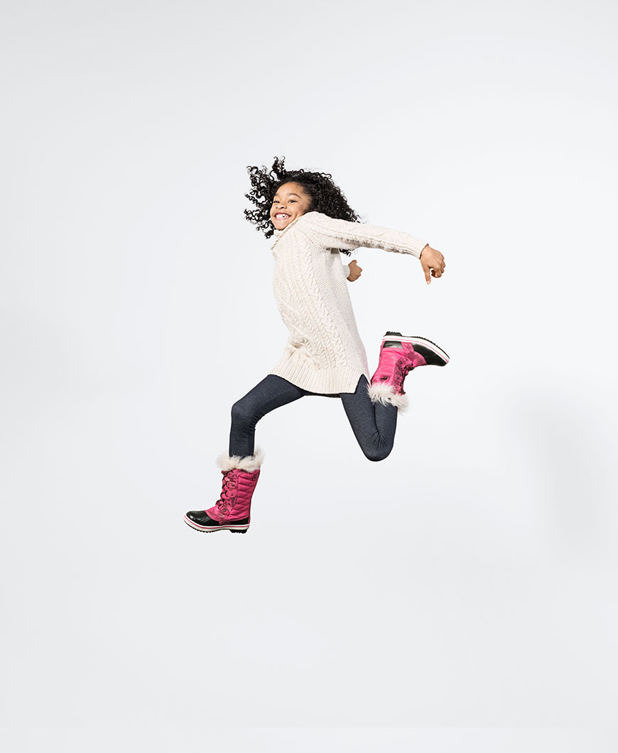 a little girl jumping wearing pink boots