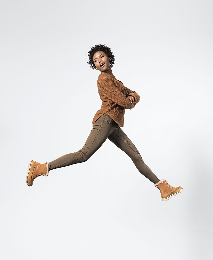 a woman jumping with brown boots