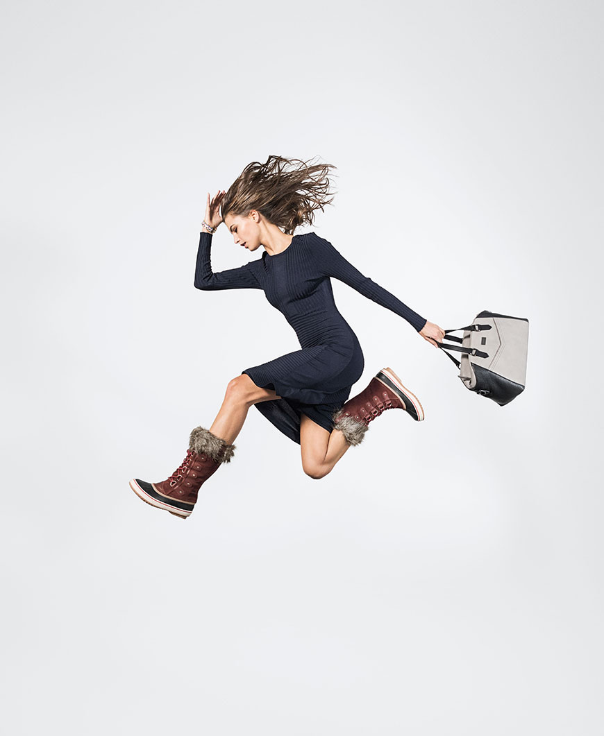 a woman jumping with burgundy boots