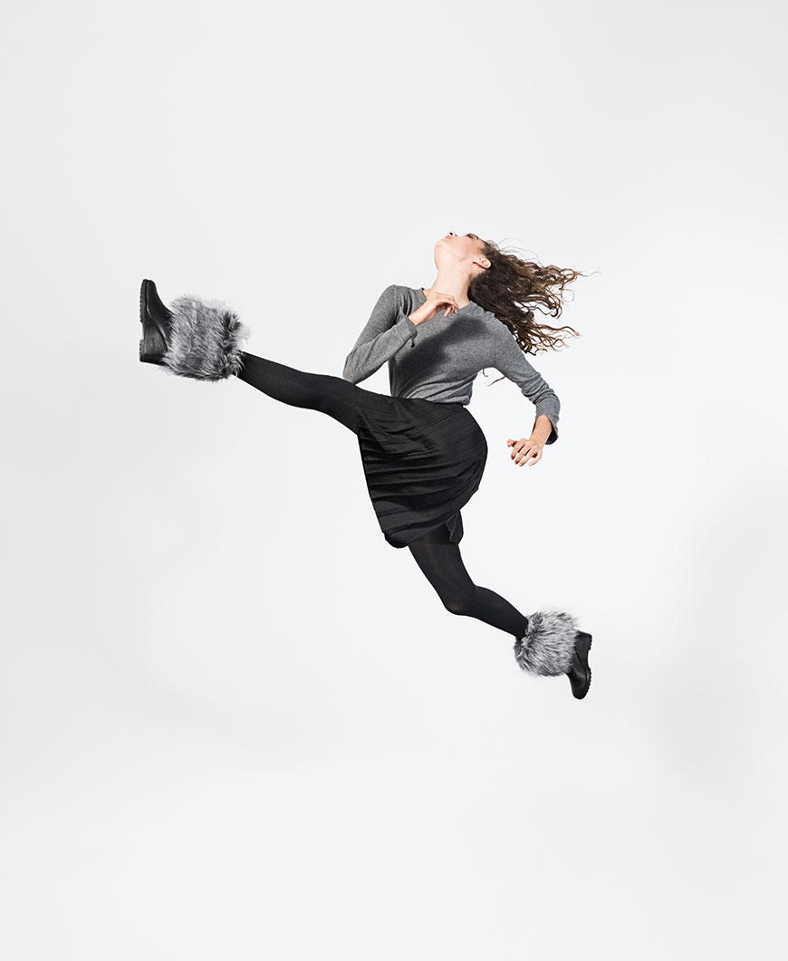 A woman jumping with black and grey boots