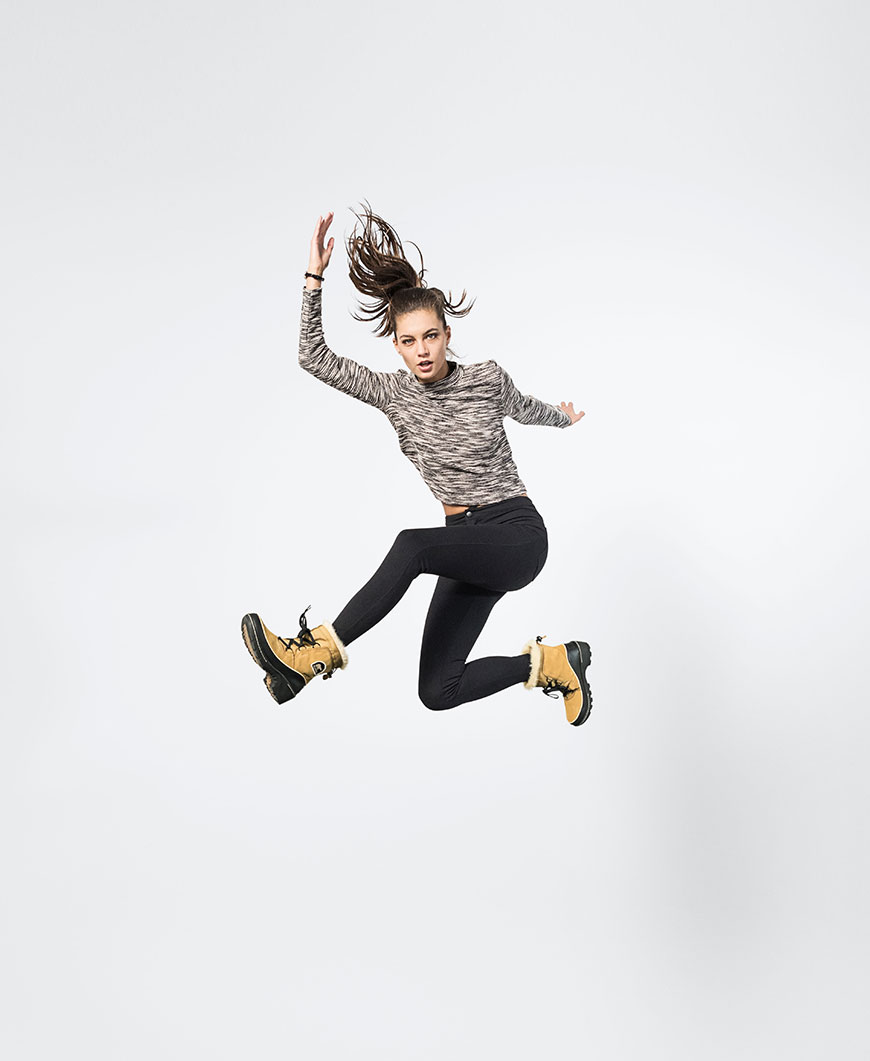 a woman jumping with black and brown boots