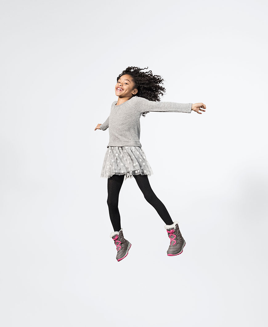 a little girl jumping wearing grey and pink boots