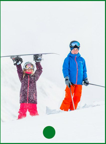 Two kids snowboarding in bright ski clothing.