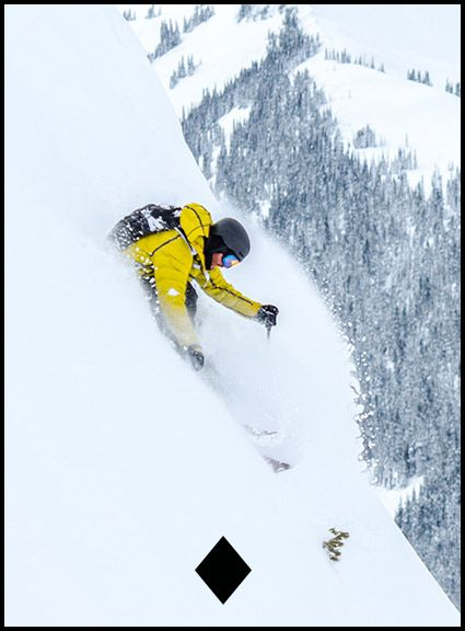 A man in a yellow coat skiing out-of-bounds.