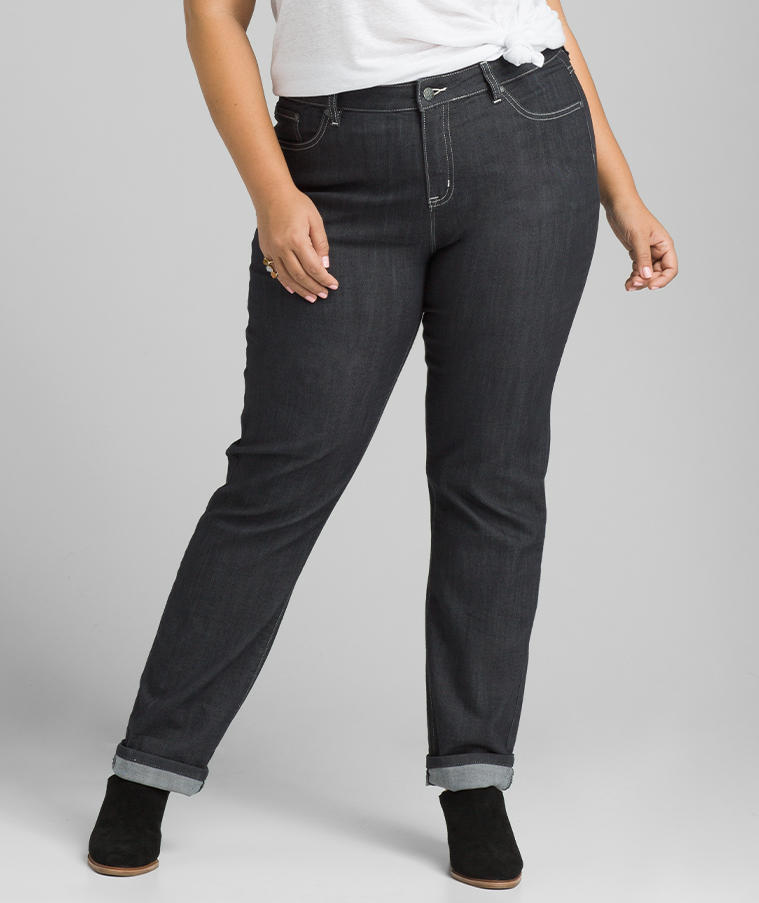 A woman wearing dark-wash denim jeans with cuff at the ankle.
