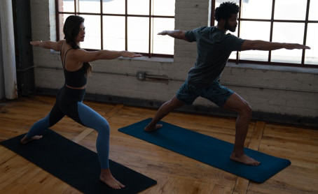 A man and women wearing yoga clothing hold a pose on their mats.