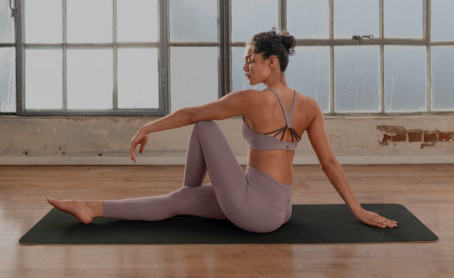 A woman wearing matching yoga pants and a sports bra holds a pose on her mat.