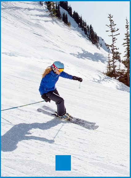 A woman in a blue coat skiing a groomed run.