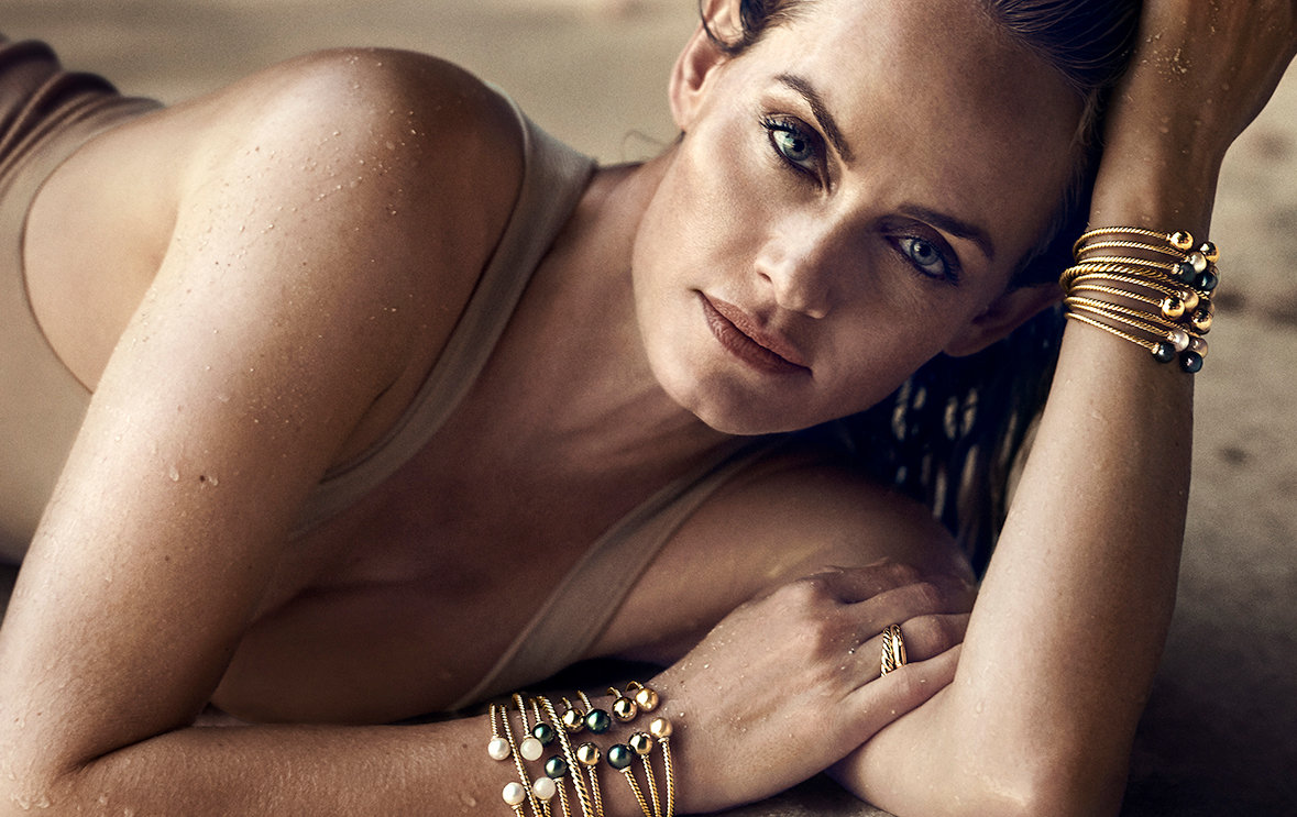 Model Amber Valetta wearing Solari earrings and bracelets in 18K yellow gold with colored gemstones on a beach.