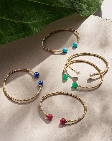 David Yurman Solari 18K黄金手链,镶嵌再造绿松石、养殖珍珠、绿玉髓、红色珐琅涂层925纯银或天青石串珠,在光线下排成一组,放置于一大片绿色树叶及其阴影下的沙色石头上。