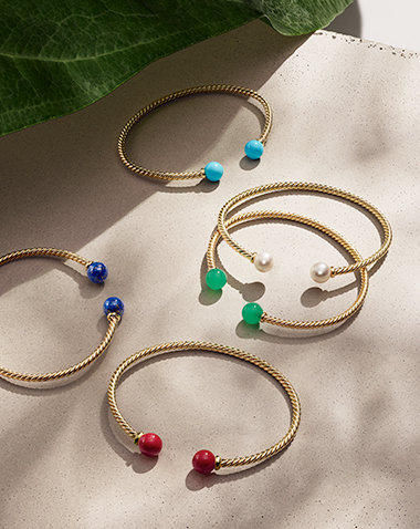 David Yurman Solari bracelets in 18K yellow gold with reconstituted turquoise, cultured pearls, chrysoprase, red enamel-coated sterling silver or lapis lazuli beads, arranged in a group in the light on a sandy-colored stone beneath a large green leaf and its shadow.