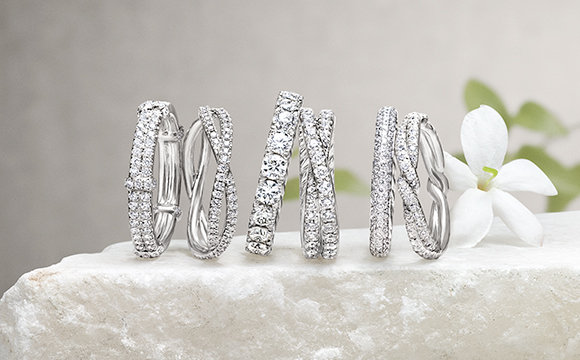 Multiple women's wedding bands in platinum with diamonds on a stone with jasmine flowers.