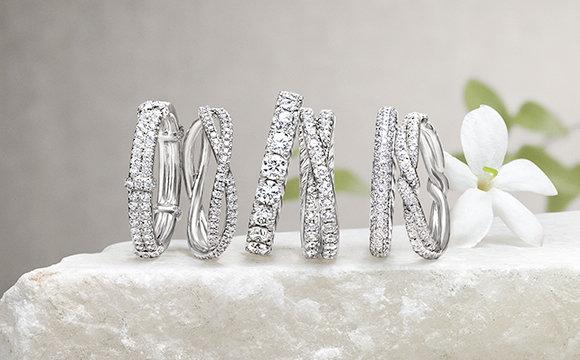 多支女士铂金钻石婚戒,与茉莉花一同摆放在一块石头上。