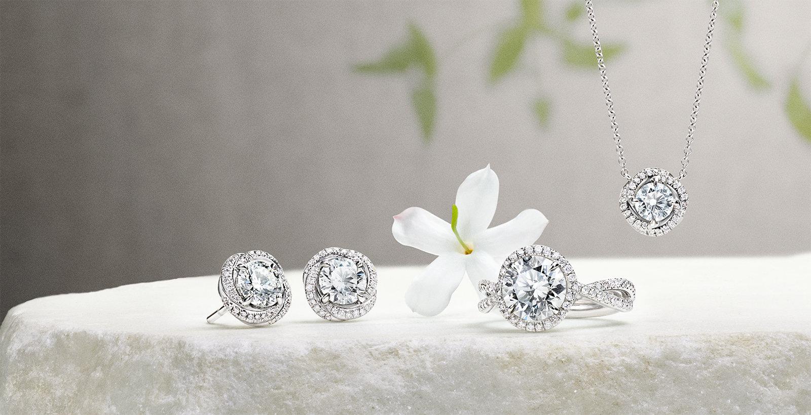 铂金钻石耳环、戒指和吊坠,与茉莉花一同摆放在一块石头上。