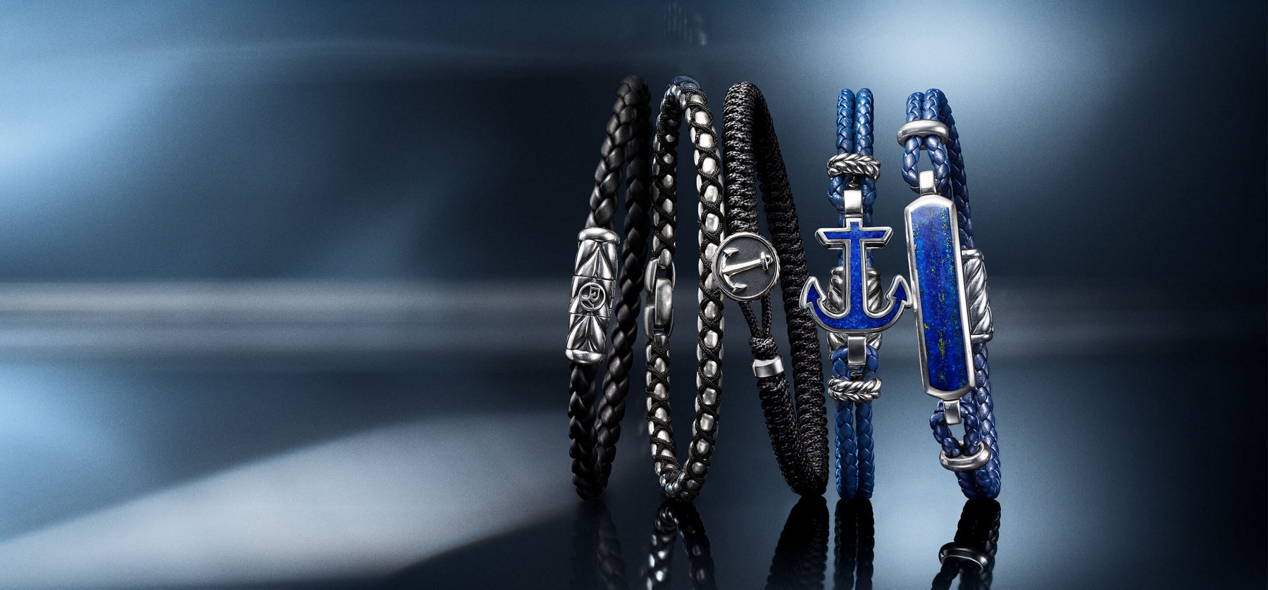 A horizontal row of David Yurman men's Chevron, Chain, Maritime® and Exotic Stone bracelets, in black rubber, black nylon or blue leather with sterling silver and lapis lazuli, on and in front of a blue background illuminated by rays of light.